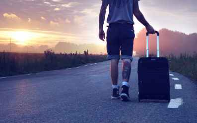 man with luggage on road during sunset