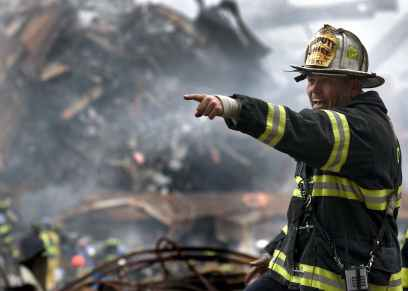 fire fighter wearing black and yellow uniform pointing for something