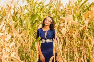 woman wearing blue dress standing in middle of corn field
