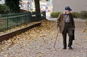photo of elderly man walking on pavement