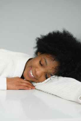 dreaming charming black woman leaning on table